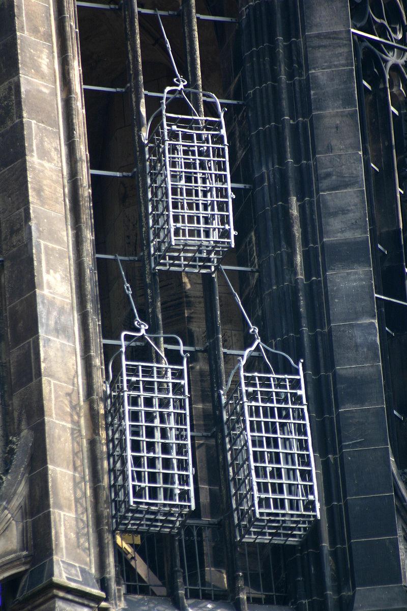 Les trois cages, encore aujourd'hui accrochées au clocher de l'église St. Lambert